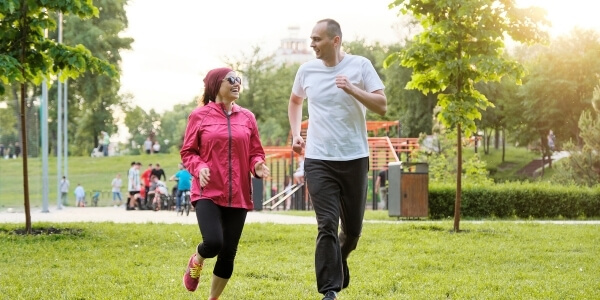 two people running in the park with a playground in the background