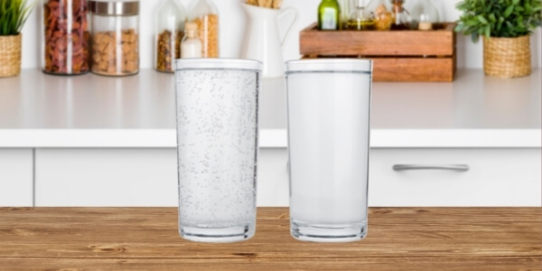 two glasses on the counter bench - one is soft drink and other is water